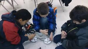 Electricians Devon, Elijah and Raneem wire the footlights.